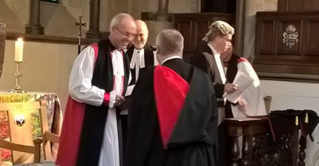 Father Robert receiving his degree from Archbishop Justin